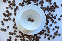 Still life with a clean coffee Cup and saucer and coffee beans scattered on the table royalty free stock photography
