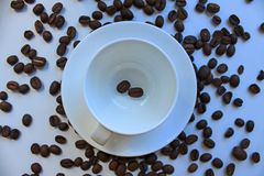 Still life with a clean coffee Cup and saucer and coffee beans scattered on the table stock photos