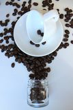 Still life with a clean coffee Cup and saucer and coffee beans scattered on the table royalty free stock photos