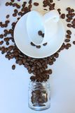 Still life with a clean coffee Cup and saucer and coffee beans scattered on the table royalty free stock image