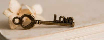 Beautiful still life Closed book, the key symbol of Valentine's Day. Vintage old heart. On a textured blue green background with. Closed book, the key symbol of Royalty Free Stock Image