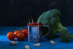 Beautiful still life in a low key. Broccoli, garlic and tomatoes. Chili pepper in a bucket. Unusual light. Royalty Free Stock Photos