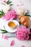 Beautiful still life with tea cup and peonies.Top view, summer french breakfast of bloger, feminine holiday morning concept stock photos