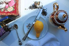 Still life with a teapot lemon Cup and scattered on a white table leaf tea royalty free stock photography