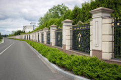 Beautiful stone fence with forged metal gates painted with gold Royalty Free Stock Images