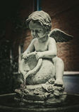 Beautiful stone fountain in the form of an angel with an amphora. Beautiful street architecture. Fountain in a stone marble statue of an angel with a tilted royalty free stock image