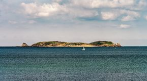 Beautiful stone island in the ocean and white yacht. Bretagne, France Royalty Free Stock Image