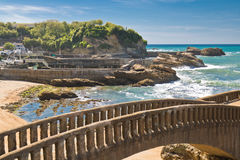 Beautiful stone walking footbridge over sandy beach in touristic destination surf spot with turquoise ocean and waves in biarritz Stock Image