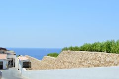 Stone wall descending down to the sea with blue water in a tropical resort and a white building with a roof of red shingles and gr. A beautiful stone wall Stock Photography