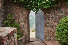 In the beautiful stone wall the iron door is ajar. In the doorway we see a river Stock Photos