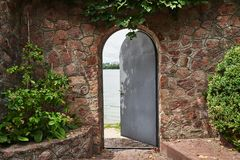 In the beautiful stone wall the iron door is ajar. In the doorway we see a river Royalty Free Stock Photography