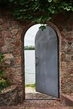 In the beautiful stone wall the iron door is ajar. In the doorway we see a river Royalty Free Stock Images