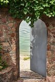 In the beautiful stone wall the iron door is ajar. In the doorway we see a river Royalty Free Stock Photo