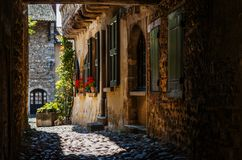 Beautiful stony street with red flowers in the medieval town. Perouges near Lyon, France Royalty Free Stock Image