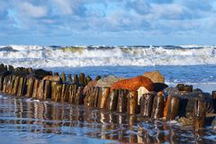 Beautiful storm at sea, breakwaters and rocks in the foreground.  royalty free stock photography