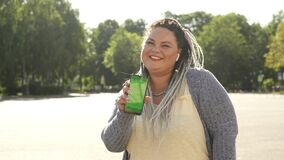 Beautiful stout girl with chromakey on her smartphone advertising mobile app. Young pretty fat woman with dreads showing