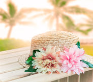 Beautiful straw hat decorated with artifucial flowers on wood ta Stock Image
