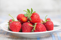 Beautiful strawberries on plate. Red fresh berries with green leaves. Shallow depth of field photography, macro view Royalty Free Stock Photos