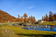 Beautiful stream on mountain with blue sky, red trees in autumn and old bridge Stock Photo
