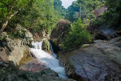 Waterfall between rocks in the jungle green forest. Beautiful stream waterfall run on the rocks in the tropical jungle green forest. Scenic water fall between Stock Image