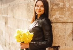 Beautiful portrait of brunette woman holding yellow spring flowers royalty free stock photography