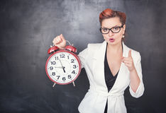 Beautiful strict teacher with clock on blackboard background Stock Photography