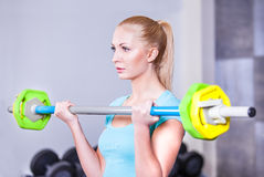 Beautiful strong blond woman with barbell Royalty Free Stock Photo