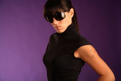 Beautiful strong brunette in sunglasses. Violet background Stock Images