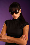 Beautiful strong brunette in sunglasses. Violet background Stock Photography