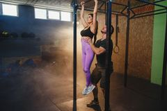 Beautiful strong muscular woman doing pull up exercise with help of personal trainer it the gym. Beautiful strong muscular women with sport wear doing pull up royalty free stock photos