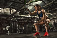 Beautiful strong sporty woman doing crossfit exercise with battle ropes stock image