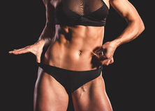 Beautiful strong woman. Cropped image of beautiful strong woman in black underwear showing her abdominal muscles, on dark background stock images