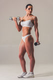 Beautiful strong woman. Full length portrait of beautiful strong woman in white underwear with dumbbells, on gray background Royalty Free Stock Image