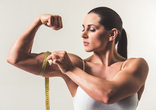 Beautiful strong woman. Is measuring her biceps, on light background royalty free stock image