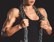 Beautiful strong woman. Beautiful strong muscular woman with iron chain on dark background Stock Photography
