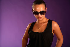 Beautiful strong woman in sunglasses. Violet background Stock Image