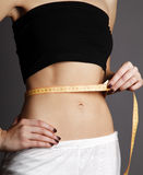 Beautiful and strong women's abs with metre. Royalty Free Stock Images