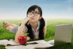 Beautiful student daydreaming on meadow Royalty Free Stock Photo