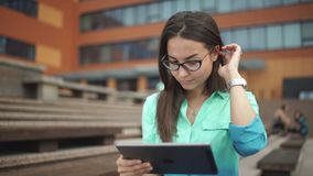 Beautiful student with a digital tablet sitting in the open space. Elegant young girl using the tablet. Beautiful student in glasses with a digital tablet stock footage