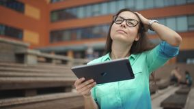Beautiful student with a digital tablet sitting in the open space. Elegant young girl using the tablet. Beautiful student in glasses with a digital tablet stock video footage