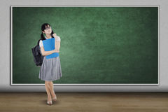 Beautiful student with empty chalkboard. Portrait of a beautiful high school student standing in the classroom with empty chalkboard Royalty Free Stock Image