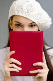Piercing eyes looking over a notebook. Stock Photo