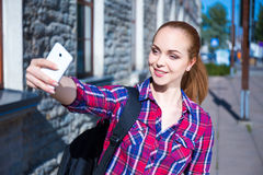 Beautiful student girl making selfie photo on mobile phone Royalty Free Stock Image