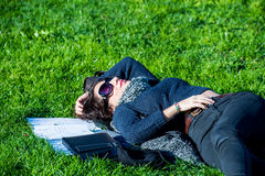 Beautiful student girl with notebooks lying on green grass and relaxing Royalty Free Stock Photos