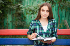 Beautiful student girl reading book outdoors. Can be used as education, leisure concept etc Stock Photo