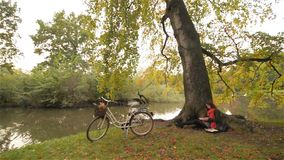 Beautiful student girl relaxing in autumn park reading book, sitting alone under tree, bicycle in the background, Sunny stock video