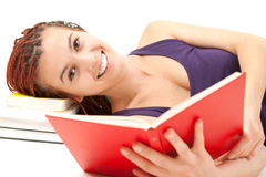 Beautiful student girl resting on stack of books, reading Royalty Free Stock Image