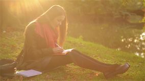 Beautiful student girl sitting on the grass and writing in a notebook in the beautiful park, lake in the background stock footage