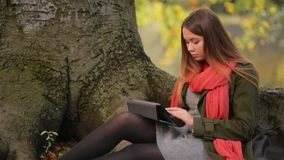 Beautiful student girl using tablet outdoor sitting on tree near lake. HD stock video
