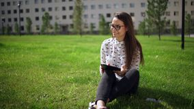 Beautiful student in glasses with digital tablet sitting on the grass stock video
